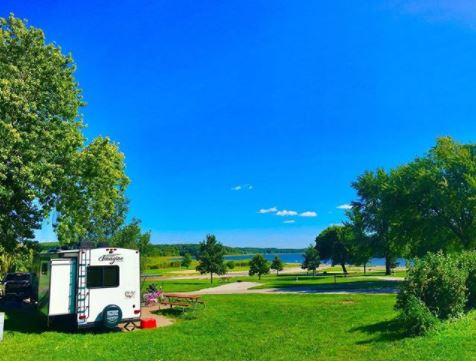 RV camper alone at campsite on green grass, under clear blue sky. Blue lake in background.