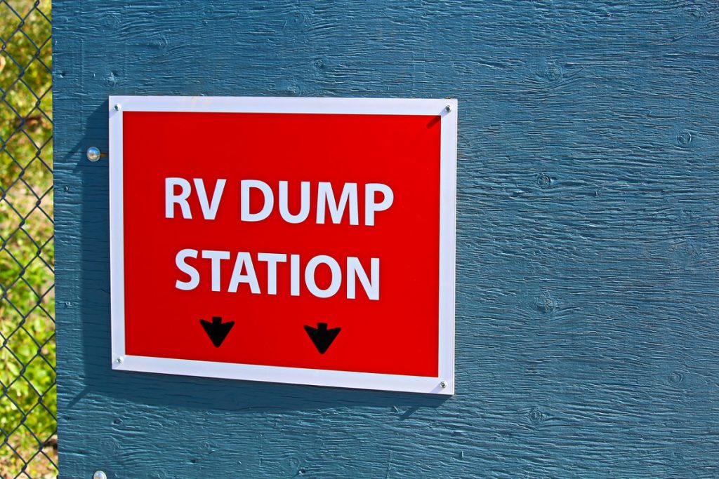 RV terms. An RV dump station sign on the edge of a building.